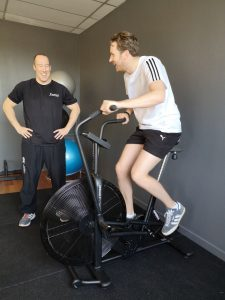 Young Man on Air bike Smiling. Perth Fitness Classes Scotland